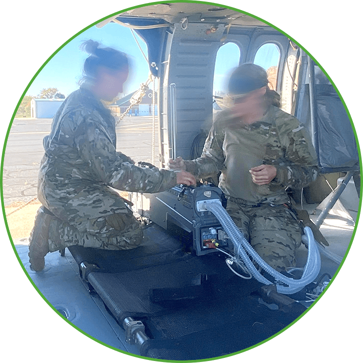 Two military personnel setting up MOVES® SLC™ inside a helicopter